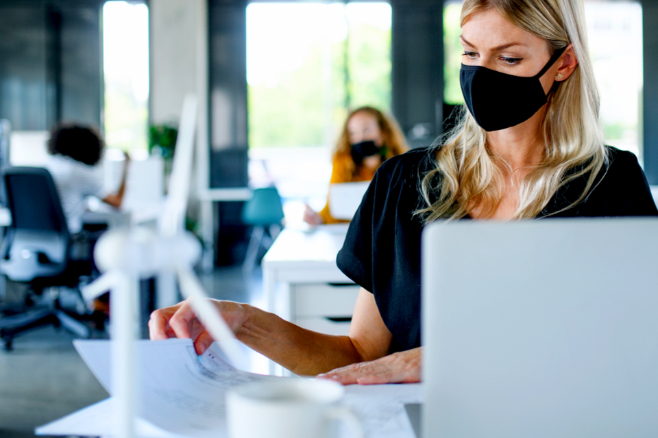 woman working in an open space while social distancing and wearing a mask