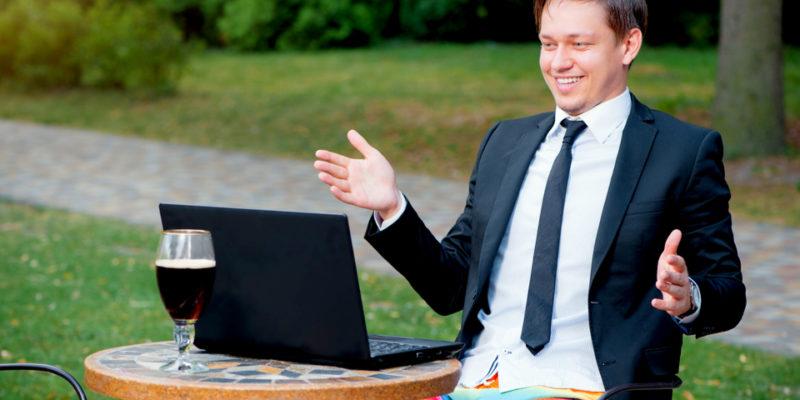 man sitting in funny swim trucks and using body language during virtual meeting
